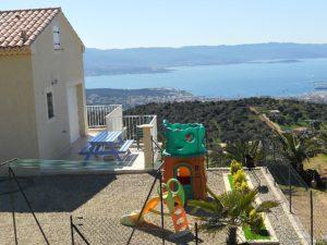 Vue extérieur sur le jardin et la terrasse de la location de vacances a Ajaccio avec vue mer.